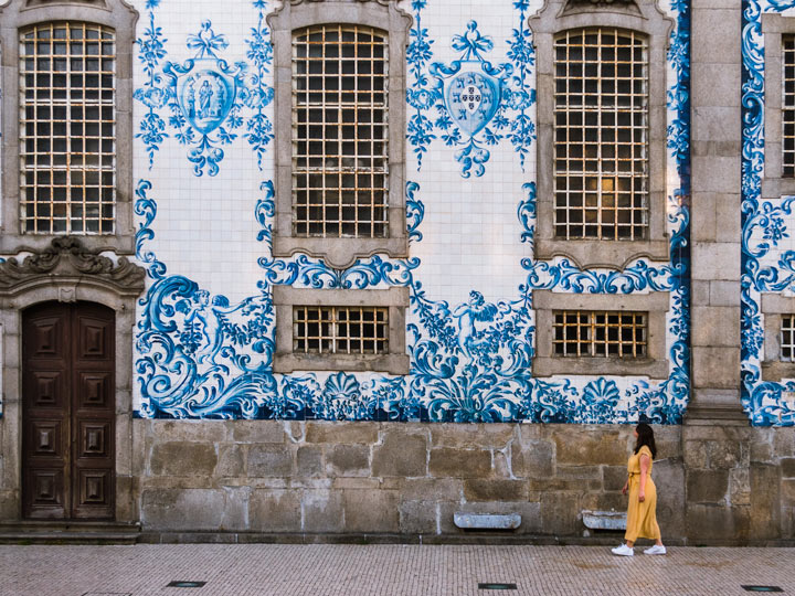 Girl in yellow dress walking past Porto church with blue and white azulejo tiles