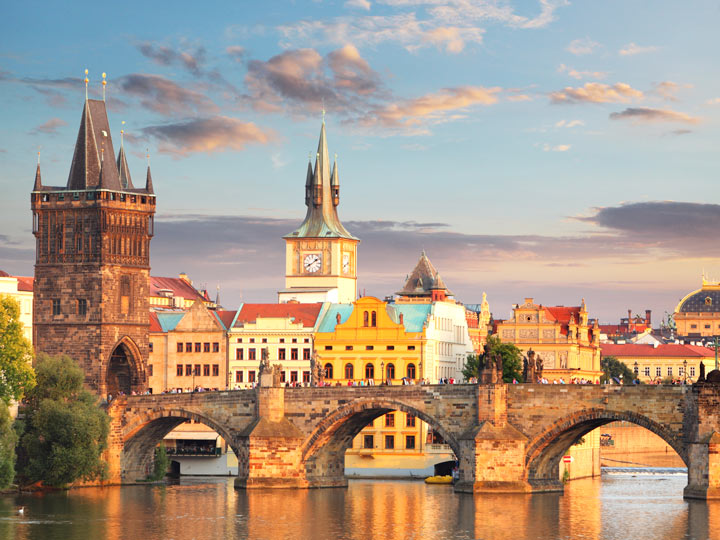 Sunrise over Prague bridge with gothic tower and houses in background