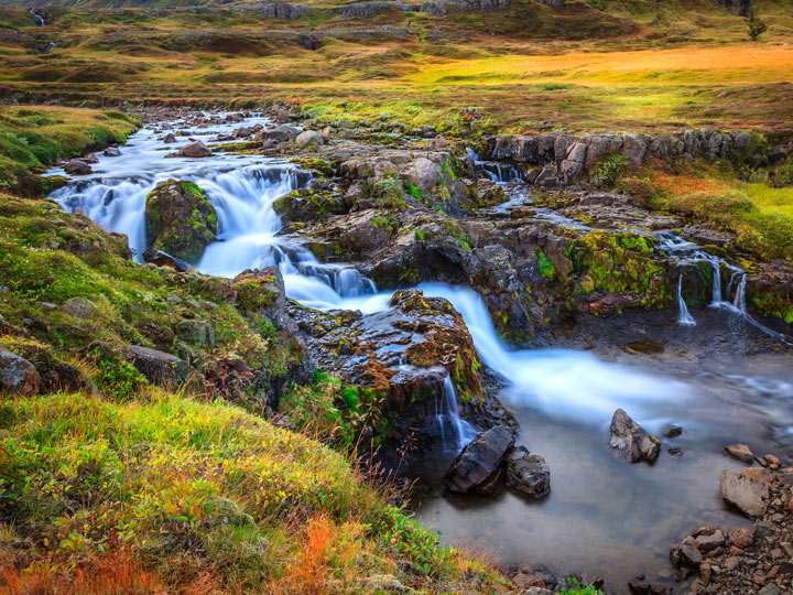 Iceland river waterfall with green and red grass surrounding pool