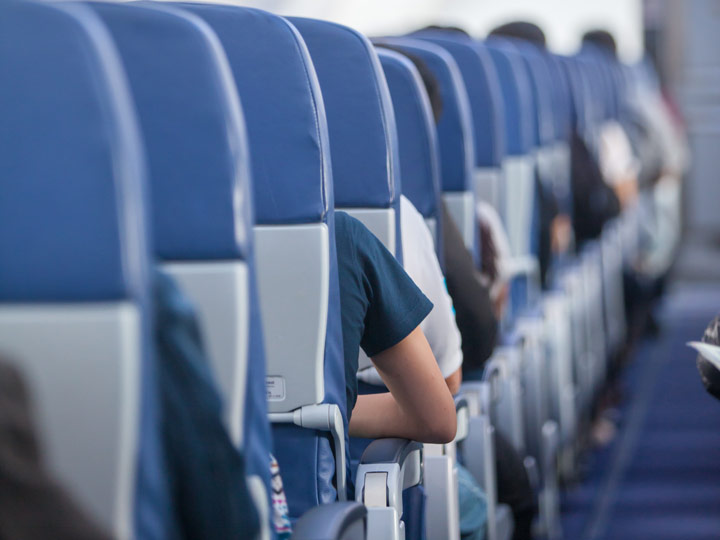 Airplane row of blue seats with armrests