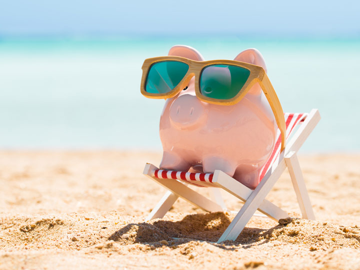 Piggybank wearing sunglasses sitting in beach chair on sand