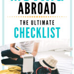 The ultimate moving abroad checklist - girl writing on notepad by suitcase