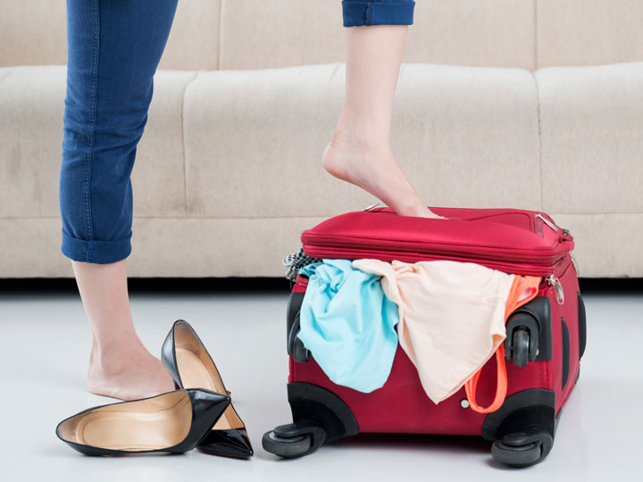 Woman standing on red suitcase full of things to bring when moving overseas