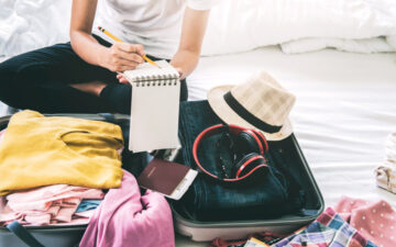 Essential MoviGirl writing moving abroad packing checklist on bed with full suitcase