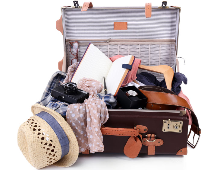 Vintage suitcase overflowing with items from moving abroad packing list