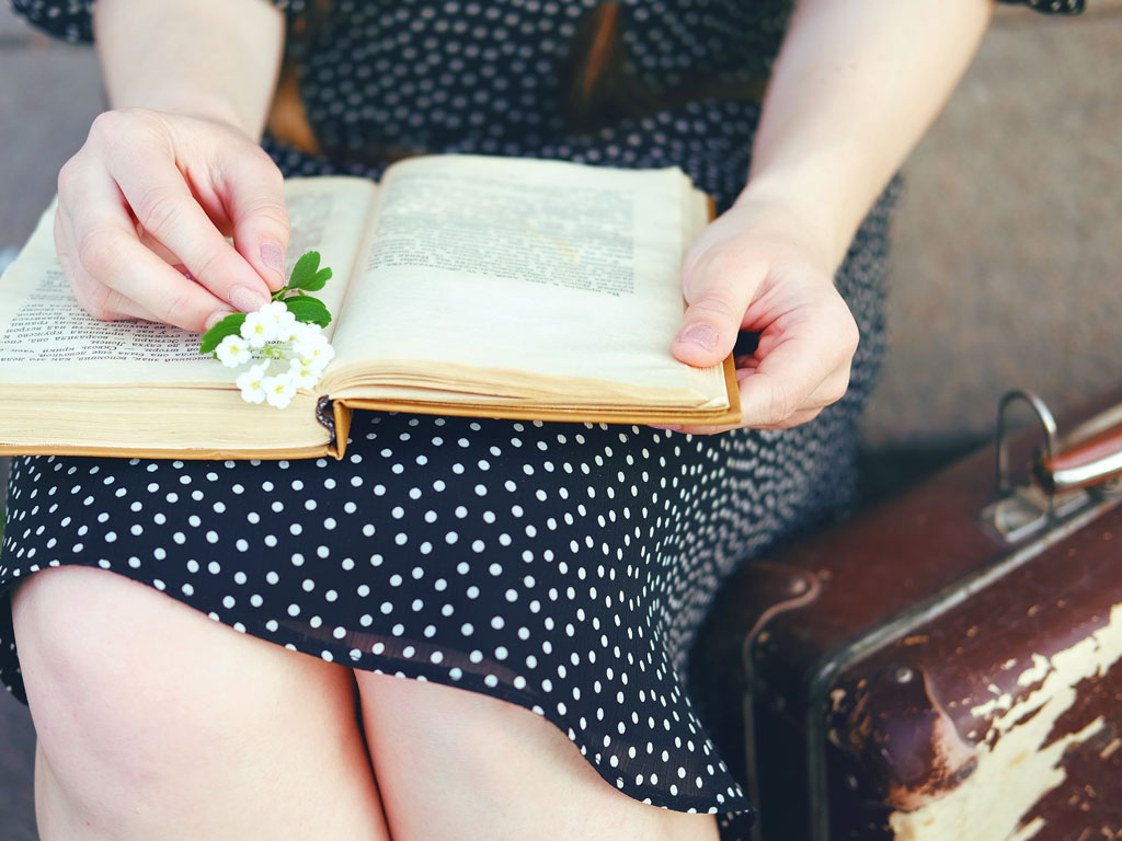 Woman in polka dot dress reading book about moving overseas after 30.