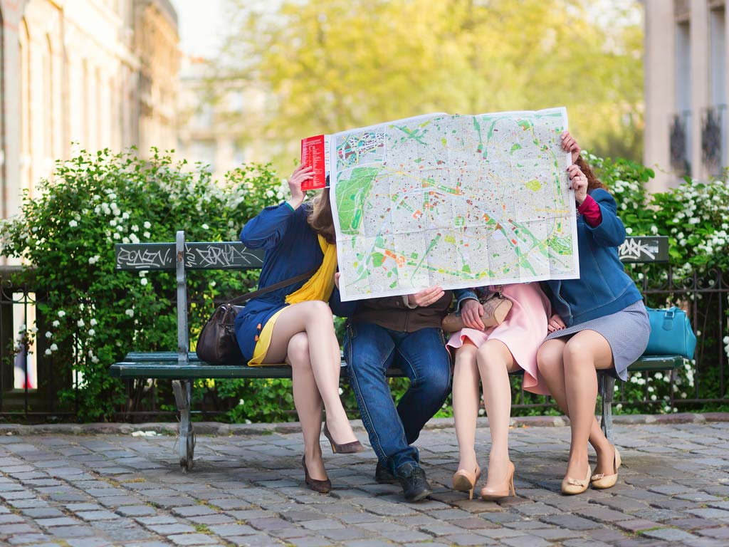 Four people living abroad in their 30s sitting on bench outside looking at large street map.