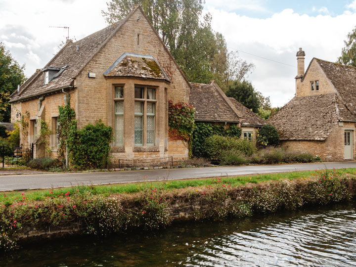 Stone cottage with ivy growing on front, behind flowing stream in Cotswolds