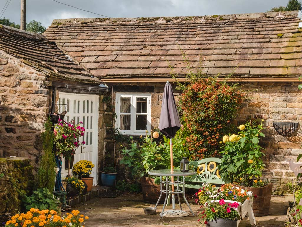 Small English stone cottage with patio garden covered in potted flowers.