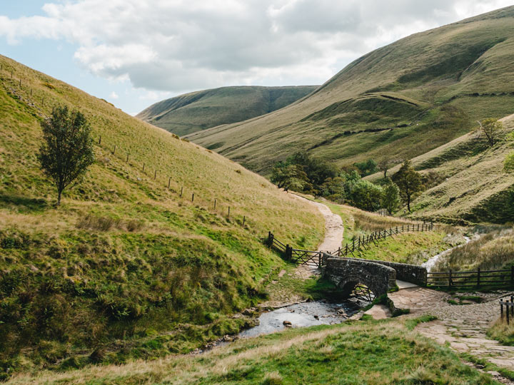 Grassy rolling hills with stream and stone bridge in Peak District England