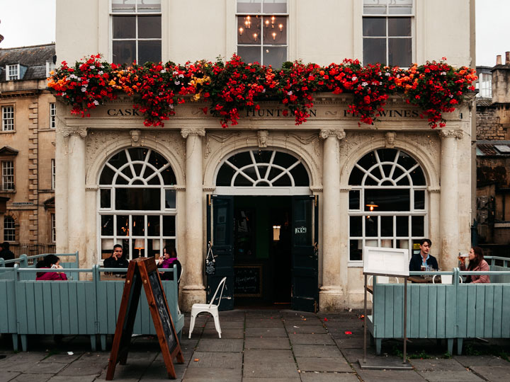 Stone facade of The Huntsman pub in Bath England, with red flowers over door