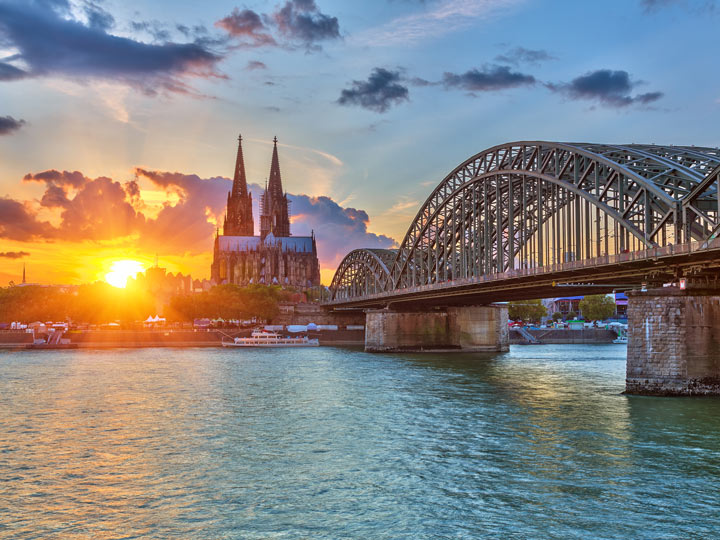 View of Hohenzollern Bridge over river with Cologne Cathedral and sunrise in background