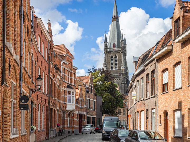 Street view of houses and distant cathedral viewed during one day in Bruges itinerary