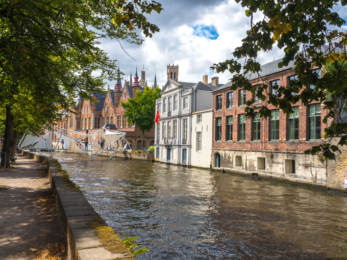 White bridge over Bruges canal, a popular sightseeing spot for a Bruges day trip