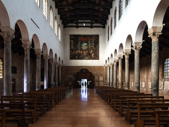 Interior aisle of Basilica di San Giovanni Evangelista with wooden benches and marble columns