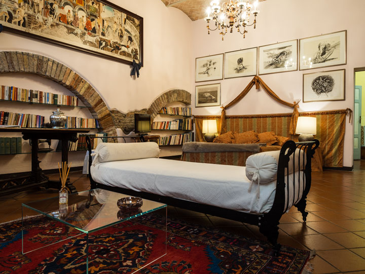 Casa Masoli room interior with lounge, bed, and bookshelves