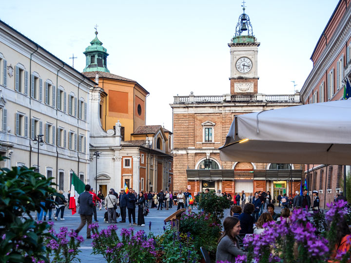 One day in Ravenna - busy town square with purple flowers and clock tower