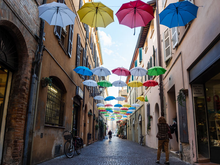 Ravenna Via Mentana umbrella street with bicycle and pedestrians