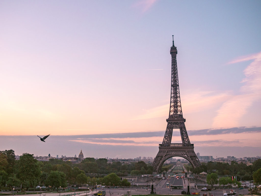 Paris Itinerary: 4 Days in the City of Light view of Eiffel Tower with purple and pink sunrise sky.