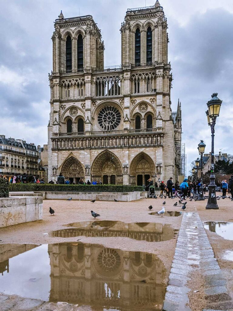 Exterior view of Notre Dame Cathedral on dark cloudy day with puddle reflection.