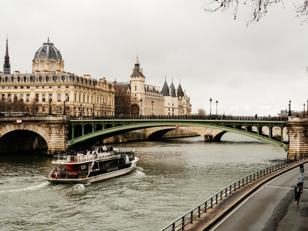 River boat traveling down Seine near green bridge