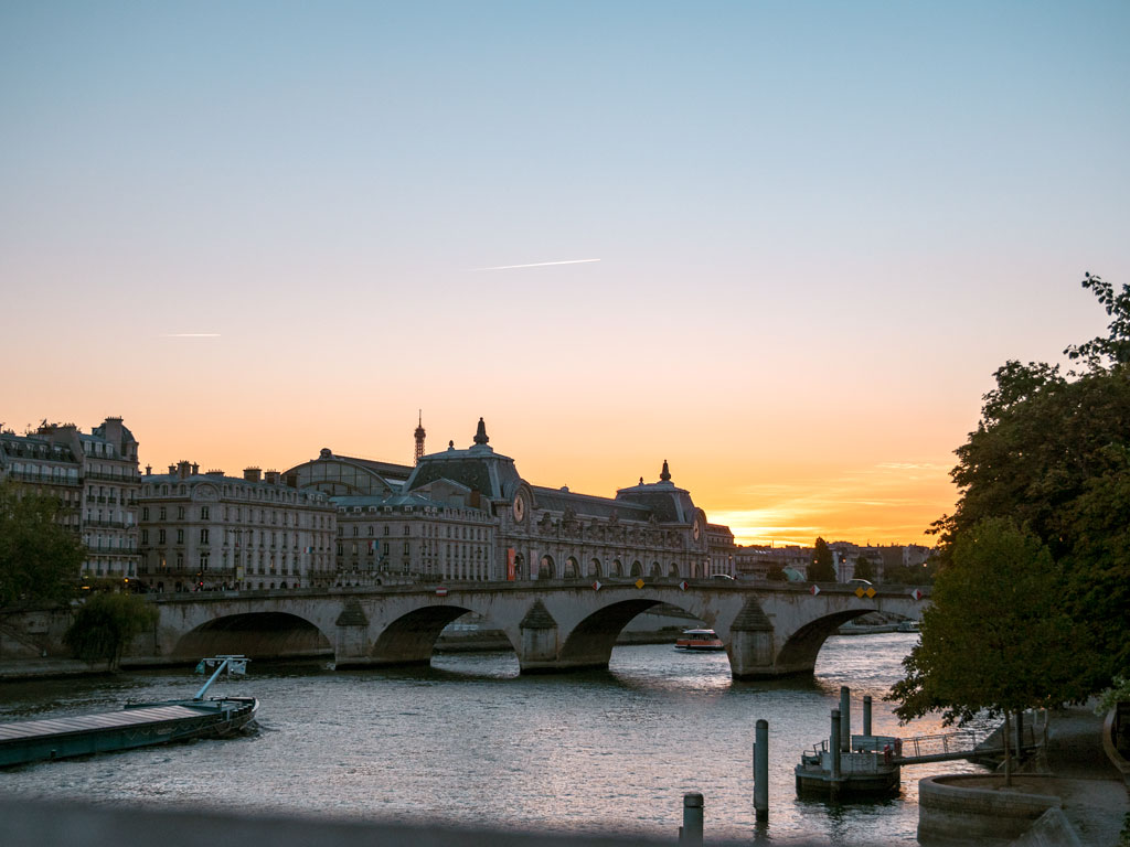 Sunset viewed from bridge over the Seine river with museum and bridge in distance.