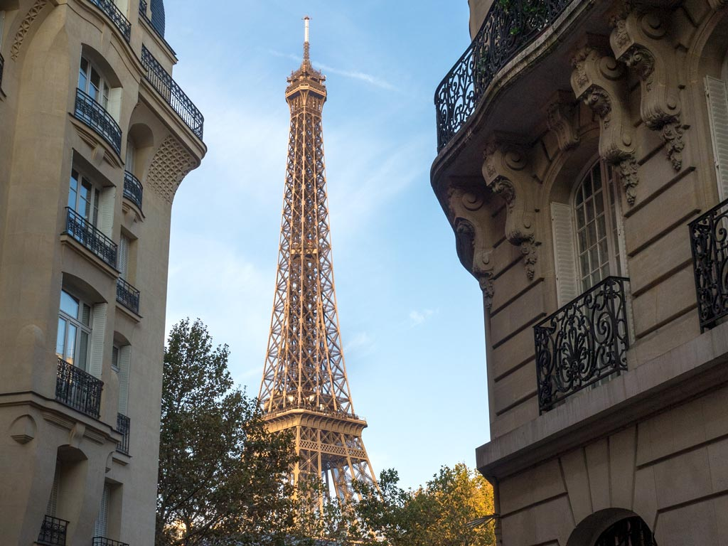 View of the Eiffel Tower between two buildings.