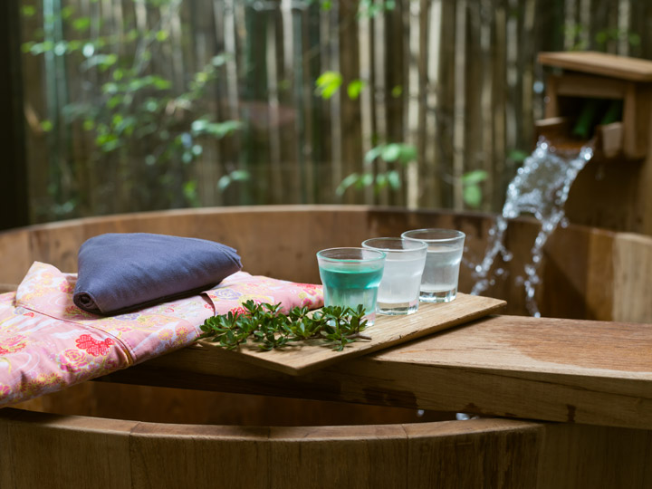 Atami onsen wooden bath with pink yukata and drinks on table