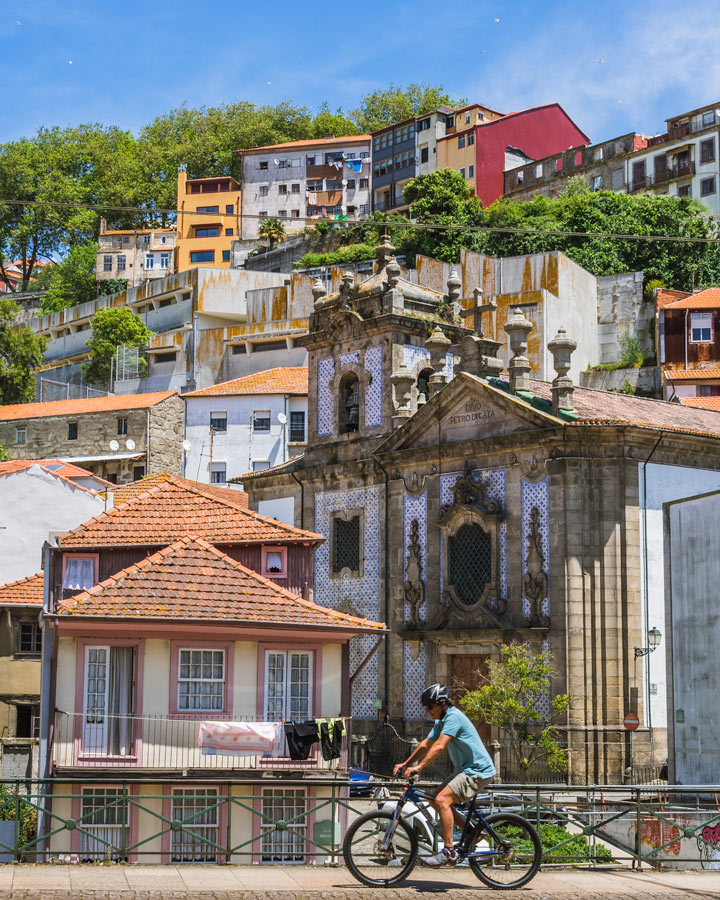 Cyclist riding in front of Porto Ribeira houses, part of Porto itinerary bike tour