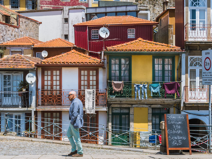 Man walking in front of colorful Porto Ribeira houses, a must see during 2 days in Porto