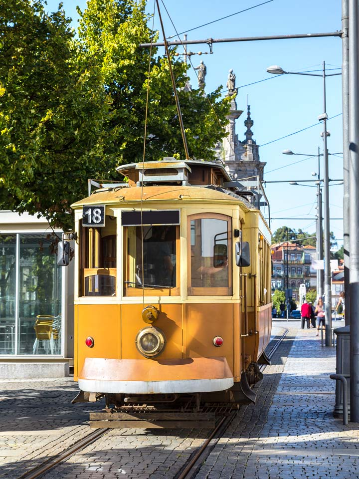 Yellow vintage tram in Porto running on tracks
