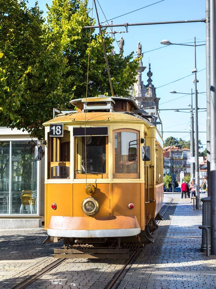 Yellow vintage tram in Porto running on tracks