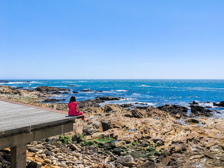 Girl in red dress sitting on Porto beach dock