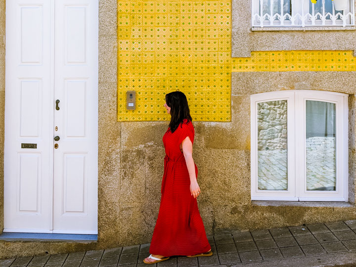 Girl in red dress in front of yellow tile wall in Foz do Douro Porto neighborhood
