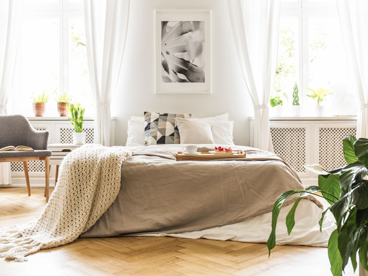 Light airy bedroom with grey bed, chair, and houseplant