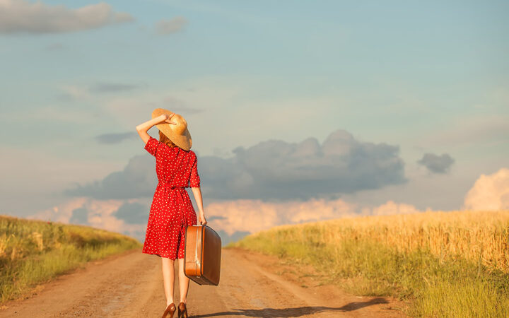 Girl in red polka dot dress holding suitcase on dirt road ready to settle into a new country