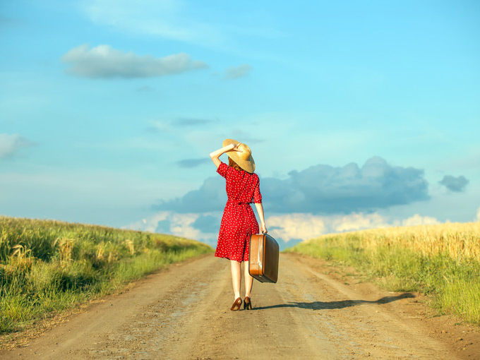 A woman starting a new life abroad with suitcase walking down dirt road