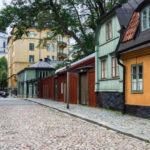 Yellow, blue, and red wood houses on cobblestone street, one of the best Stockholm photo spots
