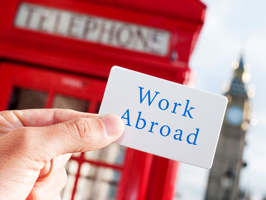 """Hand holding sign that says """"work abroad"""" in front of red phonebox."""
