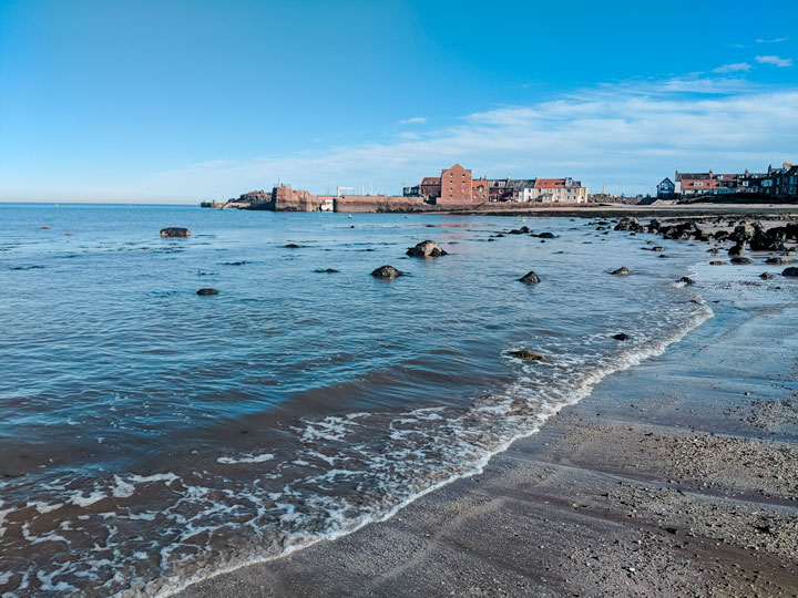 North Berwick Beach with wave coming in and village in background