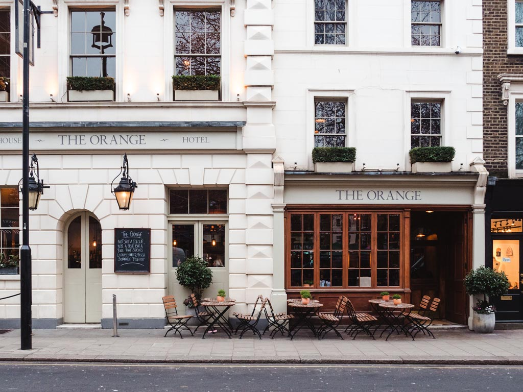 White stone exterior of hotel with outdoor cafe seating in London.