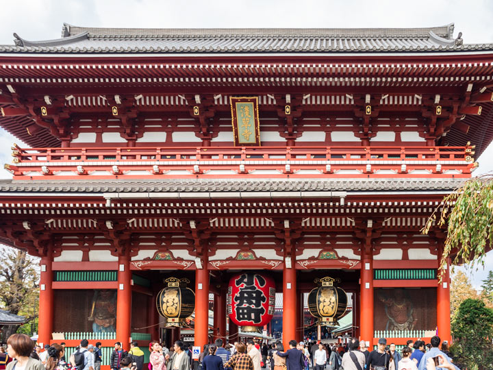 Crowd of people walking in front of Sensoji Temple with red and white facade