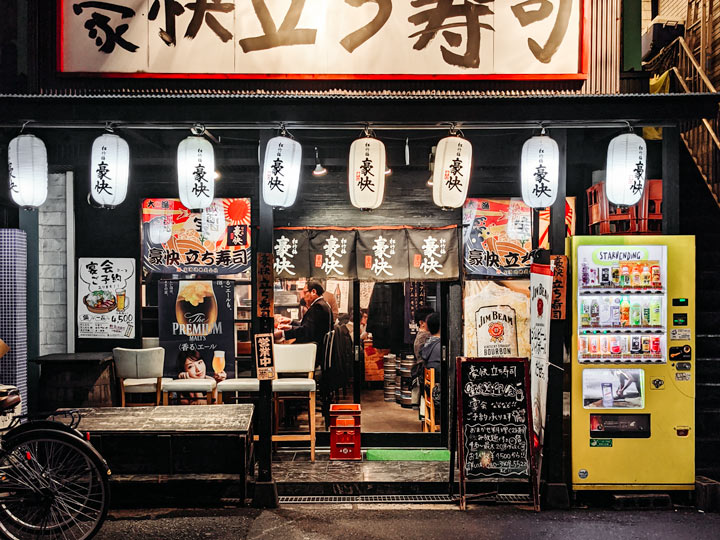 Tokyo izakaya restaurant exterior with white lanterns and vending machine
