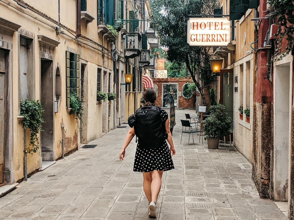 Woman walking down street in Venice wearing black travel backpack and dress.