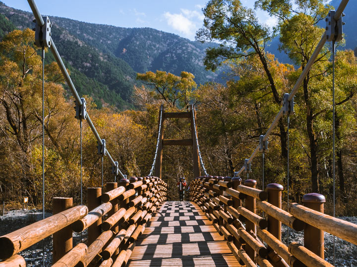 One man walking on Kamikochi bridge with autumn trees in background