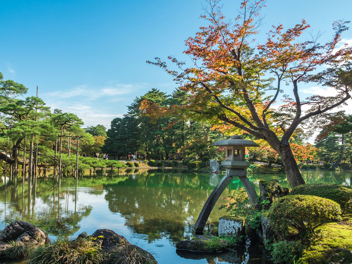 Kanazawa Kenrokuen garden pond with moss rocks and Japanese maple