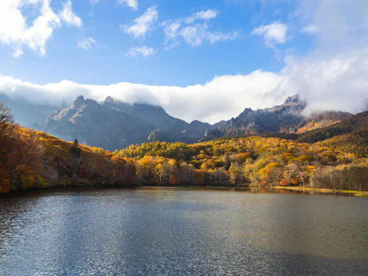 Togakushi mirror lake with autumn trees and partly cloudy sky