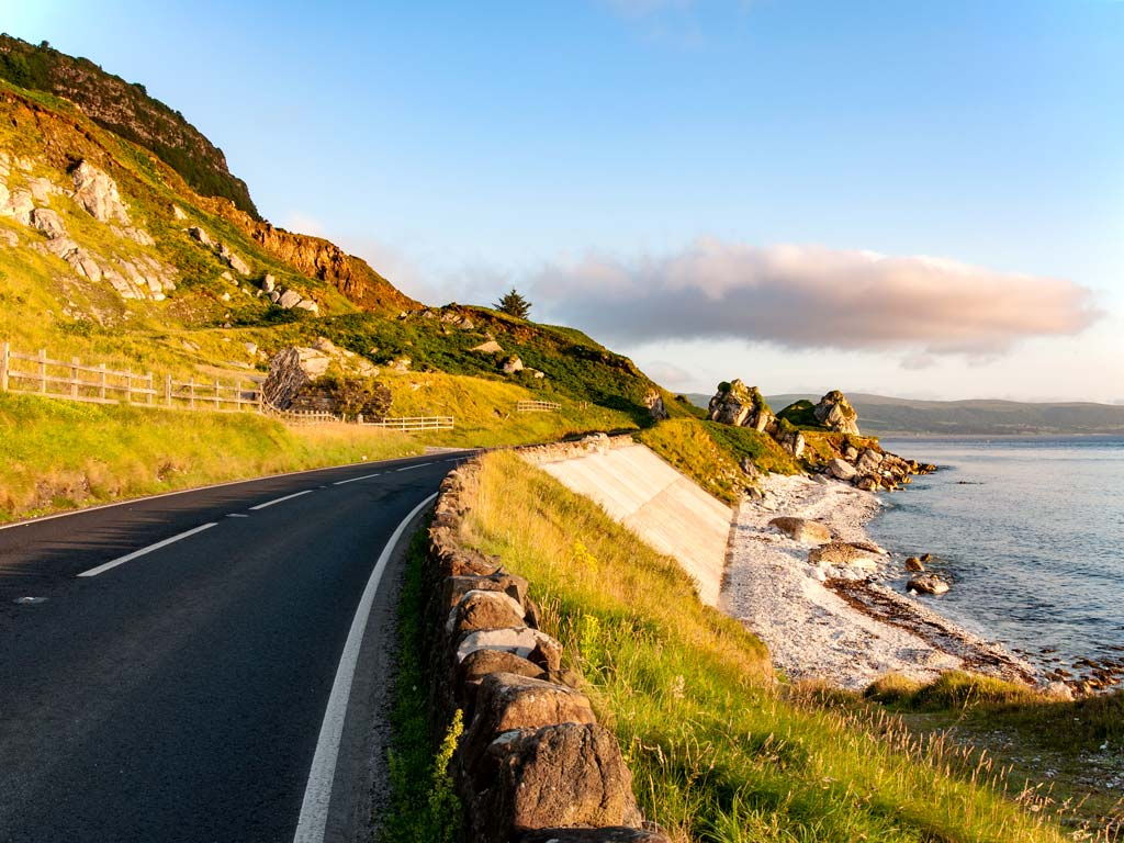 Antrim coast road with view of ocean at sunset.