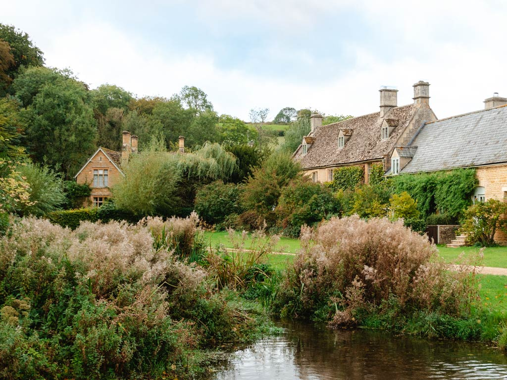 Cotswolds stone cottages with pond and foliage in foreground.