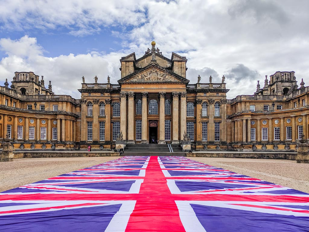 Exterior of Blenheim Palace with union jack flag runner, among the top uk bucket list ideas in England.